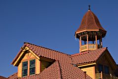 Yellow and Red Rooftop. Horizontal view of red tile roof on yellow building with bell tower Royalty Free Stock Photos