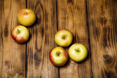 Yellow-red seasonal apples on the background of burned boards. T Royalty Free Stock Images