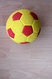 Yellow red soccer ball on wood Royalty Free Stock Images