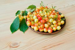 Yellow-red sweet cherry in a plate on a wooden table.  stock image