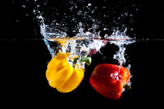 Yellow and red sweet pepper splash into a black color. Of water Stock Photos