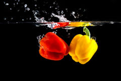 Yellow and red sweet pepper splash into a black color. Of water Stock Photography