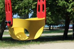 Yellow and red swing for a young child with no one in it stock image