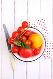 Yellow and red tomatoes, basil and mozzarella cheese. On a white wooden table Stock Photo