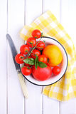 Yellow and red tomatoes, basil and mozzarella cheese. On a white wooden table Stock Image