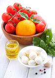 Yellow and red tomatoes, basil and mozzarella cheese. On a white wooden table Royalty Free Stock Image