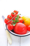 Yellow and red tomatoes, basil and mozzarella cheese. On a white wooden table Royalty Free Stock Photography