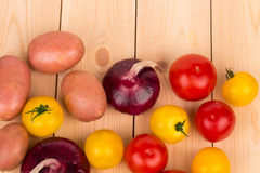 Yellow and red tomatoes onion on the wood. Royalty Free Stock Images