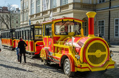 Yellow and red touring car in the form of a train with carriages waiting for tourists landing on a tour is a sunny day at the Mark Royalty Free Stock Photography