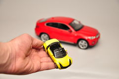 Yellow and red toy car. Yellow car on palm, red car in the background Stock Images