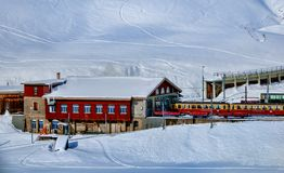 Yellow and Red Train Beside Snowy Mountain stock image