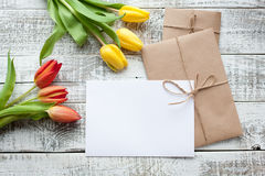Yellow and red tulip bouquet and blank greeting card. Top view over wooden table Stock Photo