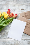 Yellow and red tulip bouquet and blank greeting card. Top view over wooden table Stock Photography