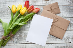 Yellow and red tulip bouquet and blank greeting card. Top view over wooden table Royalty Free Stock Photo