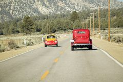 A yellow and red VW hotrod drives in opposite direction of a restored bright Red Roadster hotrod pickup truck along rural highway  Stock Photography