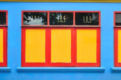 Yellow and red window on a blue wall. Stock Image