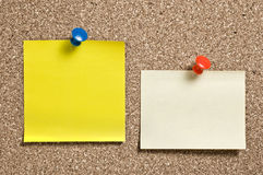 Yellow remainder notes. On cork board, with tacks Stock Images