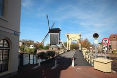Ancient city hall at the Breestraat in the inner city of the town Leiden in the Netherlands. The yellow Rembrandtbrug and windmill De Punt in the city of Leiden stock photography
