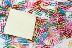 Yellow reminder sticker on the pile of paperclips Royalty Free Stock Images