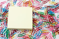 Yellow reminder sticker on the pile of paperclips Stock Image