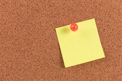 Yellow reminder sticky note on cork board. Empty space for text stock image