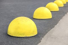 Yellow restrictive hemispheres in the parking area of the car, and the repair area of the road surface in the city stock photos