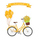 Yellow retro bicycle with tulip bouquet in floral basket and balloons attached to the trunk Royalty Free Stock Images