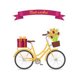 Yellow retro bicycle with tulip bouquet in floral basket and giftbox on trunk Royalty Free Stock Photography