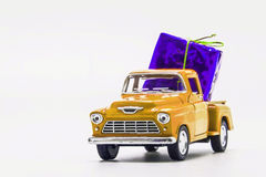 Yellow retro car pickup violet gift box isolated.  stock photography