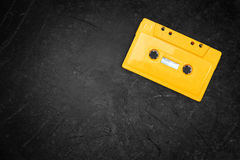 Yellow retro Cassette tape over blackboard. top view Royalty Free Stock Image
