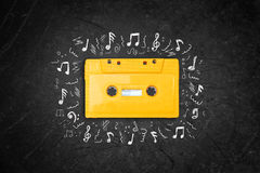 Yellow retro Cassette tape over blackboard. top view. music sketches Royalty Free Stock Photography