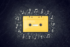 Yellow retro Cassette tape over blackboard. top view. music sketches. Royalty Free Stock Photography