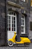 A yellow retro style model scooter in Essen. A yellow old model scooter locked to a rain pipe of a historic house in the center of the german city of Essen royalty free stock photo