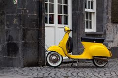 A yellow retro style scooter in Essen. A yellow retro style scooter locked to a rain pipe of a historic house in the center of the german city of Essen royalty free stock images