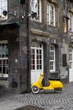 Yellow retro style scooter parked. A yellow old model scooter locked to a rain pipe of a historic house in the center of the german city of Essen stock photos