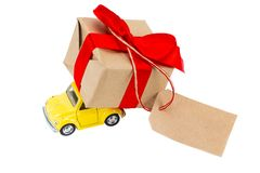 Yellow retro toy car delivering gifts box with tag with empty sp. Ace for a text on white background royalty free stock photography