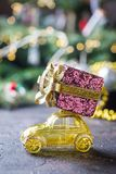 Yellow retro toy car. Delivering Christmas or New Year gifts on dark background royalty free stock images
