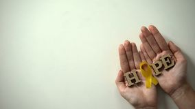 Yellow ribbon and hope word in hands, childhood cancer awareness, healthcare. Stock photo royalty free stock images