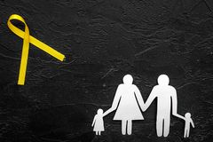 Yellow ribbon for suicide and endometriosis awareness near paper silhouette of family on black background top view.  Royalty Free Stock Photography