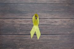 Yellow ribbon symbolic color for Sarcoma Bone cancer, Bladder cancer, Liver disease, Spina Bifida Awareness. Month and suicide prevention on helping hand royalty free stock photo