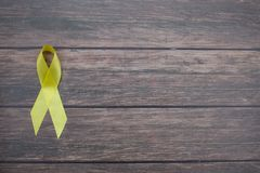 Yellow ribbon symbolic color for Sarcoma Bone cancer, Bladder cancer, Liver disease, Spina Bifida Awareness. Month and suicide prevention on helping hand royalty free stock photos