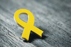 Yellow ribbon on a wooden surface. Closeup of a yellow ribbon on a gray rustic wooden surface, with some blank space on the right Royalty Free Stock Image