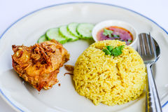 Yellow rice with fried chicken on dish. Stock Photos
