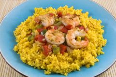 Yellow Rice and Shrimp on Blue Plate. Turquoise-colored dinner plate with crackled glaze holding dinner of yellow Spanish rice, cooked red and green peppers Royalty Free Stock Image