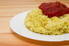 Yellow rice. In white plate on wooden table royalty free stock images