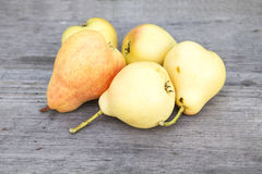 Yellow ripe pear. Lie on a wooden table Stock Photography