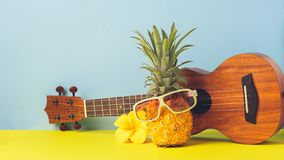 Yellow ripe pineapple in sunglasses. Guitar on yellow blue background. Funny mordashkaiz tropical fruit. Concept royalty free stock photography