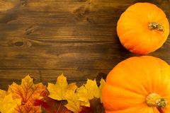 Yellow ripe pumpkin, maple leaves on wooden background. Thanksgiving Royalty Free Stock Photos