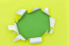 Yellow ripped open paper on green paper background. Royalty Free Stock Photography