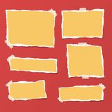 Yellow ripped strips, notebook, note paper for text or message stuck with sticky tape on bright red background. Yellow ripped strips, notebook, note paper for Royalty Free Stock Image